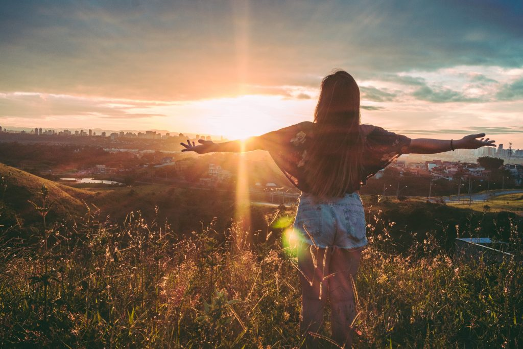 Woman with spread out arms-sunset-the-beauty-of-now